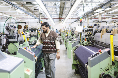 male factory worker monitoring weaving machine