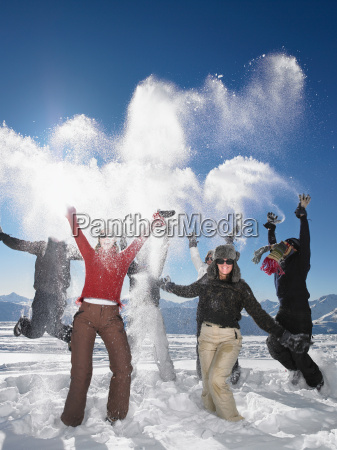 group throwing snowballs in air