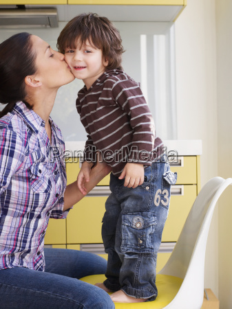 mother kissing young boy