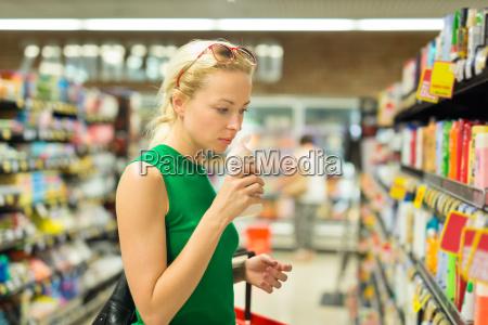 frau einkaufen persoenliche hygieneprodukte im supermarkt