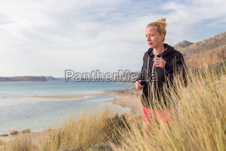 active woman jogging on beach