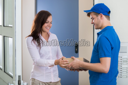 delivery man gibt package to woman