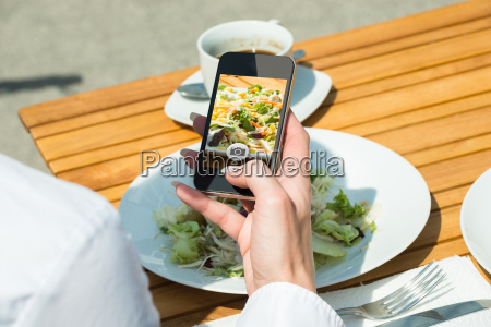 persons hand taking picture of food