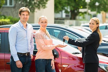 dealer giving car key zum paar