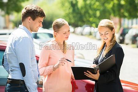 saleswoman explaining contract paper to couple