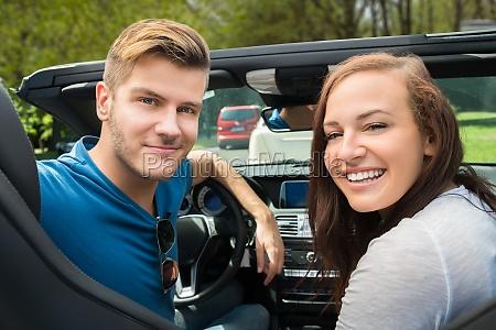 laechelnde paare die in einem auto