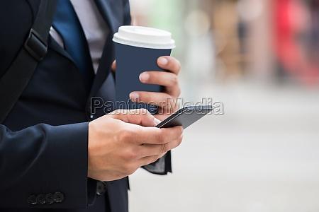 wirtschaftler hand mit handy und kaffeetasse