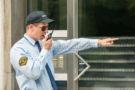 male security guard using walkie talkie