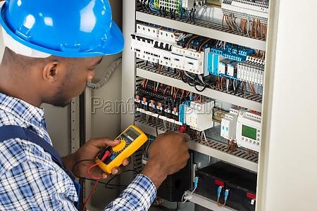 elektriker der sicherungskasten mit multimeter ueberprueft