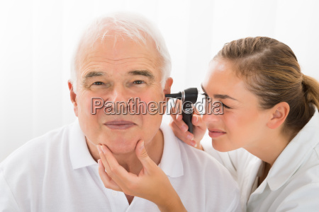 doctor looking at patients ear through