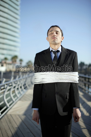 business man tied up with ropes