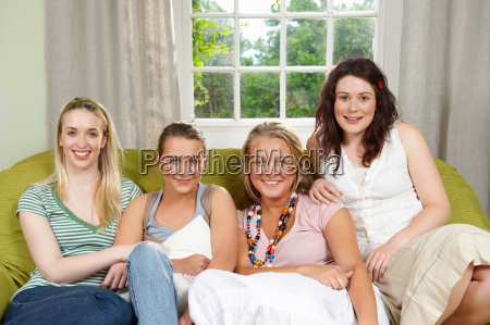 four young women seated on couch