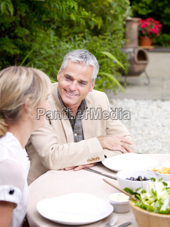 man and woman sitting outside in
