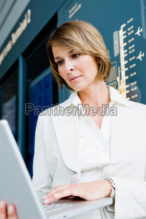 woman holding up a laptop working