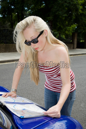 young woman reading map on electric