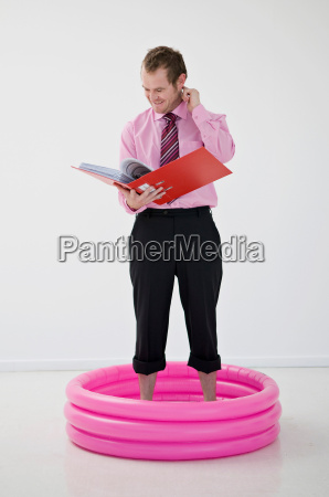 business man standing in paddling pool