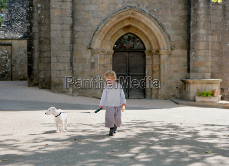 young boy walking dog