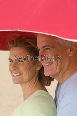 couple sheltering under beach parasol