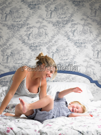 boy jumping on his mothers bed