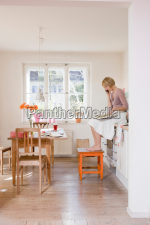 woman in kitchen talking on a