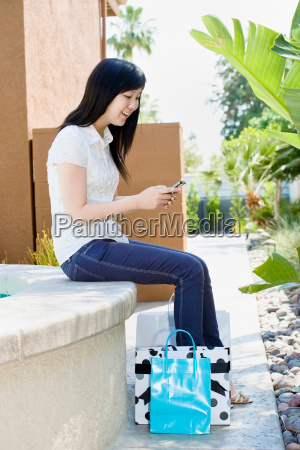 teen with shopping bags text messaging