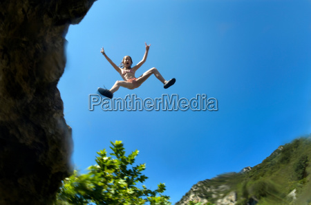 young girl jumping of a cliff
