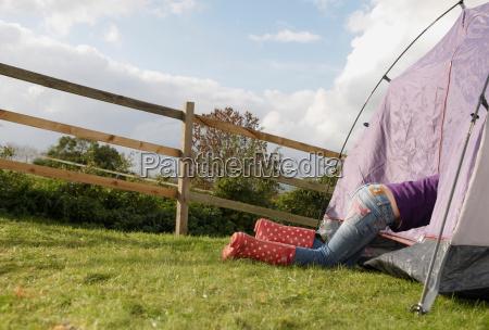 girl climbing into tent