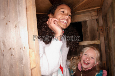 two young girls at treehouse door