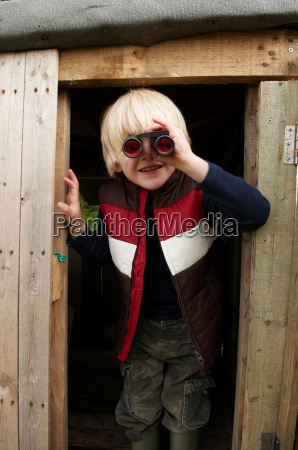 young boy with binoculars in treehouse