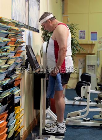 senior man on scales at gym