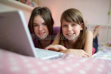 teenage girls using laptop