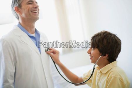 boy listening to male doctors heart