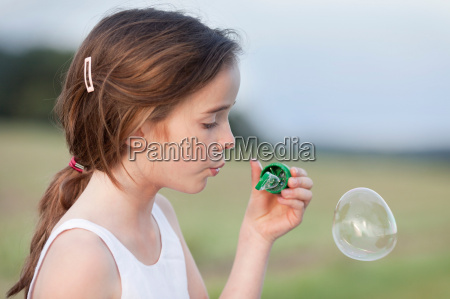young girl playing with soap bubbles
