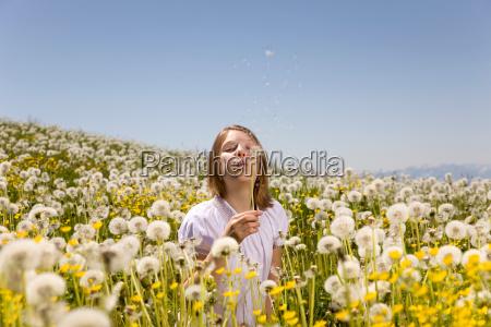 girl in meadow blowing dandelion seeds