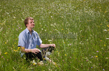 man sitting in grass with spring