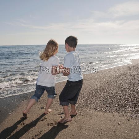 boy and girl running on beach