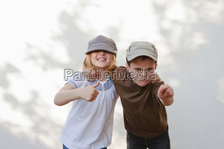 boy pointing with girl giving thumbs