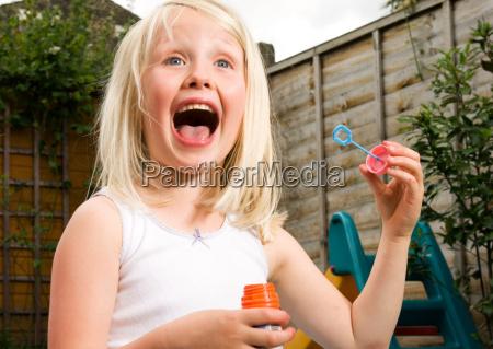 young girl having fun blowing bubbles