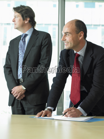business man signing papers with partner