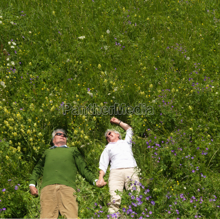 senior couple lying in field of