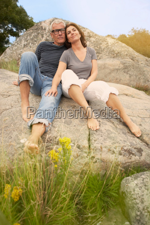 middle aged couple cuddling on rocks