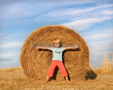boy standing in front of hay