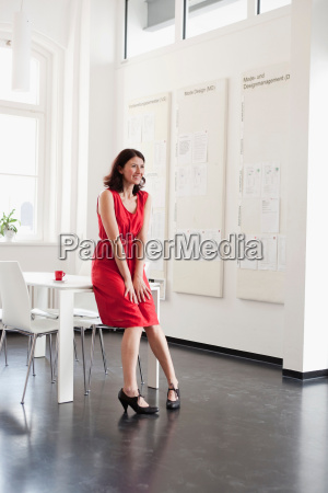 woman in red dress leaning at
