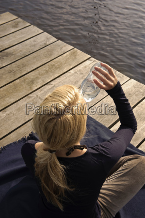 young woman sitting on blanket drinking