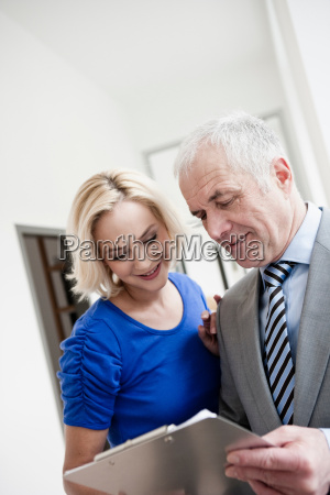 businessman and woman with clipboard