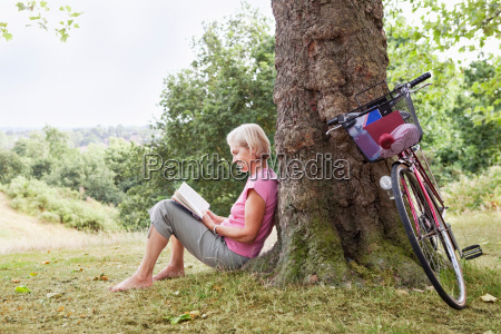 mature woman reading book in park