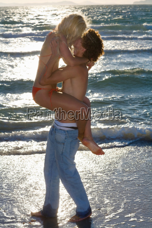 young cple kiss at sunset beach