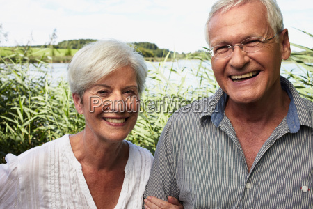 senior couple outdoors smiling to camera