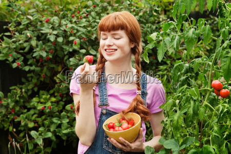 woman looking at homegrown strawberry