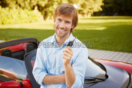 man proudly showing his key to
